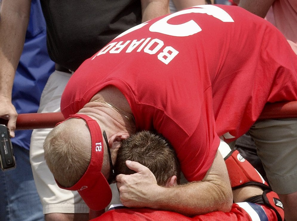 2004: Former Cornell lacrosse player Gary Malm leans down from the stands to hug senior Andrew Collins after Cornell's 6-5 loss to Navy. Malm coached senior Mike Riordan in high school and traveled from northern Virginia to see the game and was one of many fans wearing a No. 21 George Boiardi shirt.