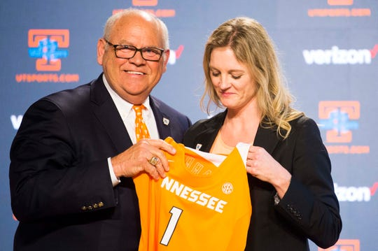 University of Tennessee athletic director Phillip Fulmer passes a jersey to Kellie Harper during a press conference announcing her as new head coach of the Lady Vols, in the Ray and Lucy Hand Studio on University of Tennessee's campus Wednesday, April 10, 2019.