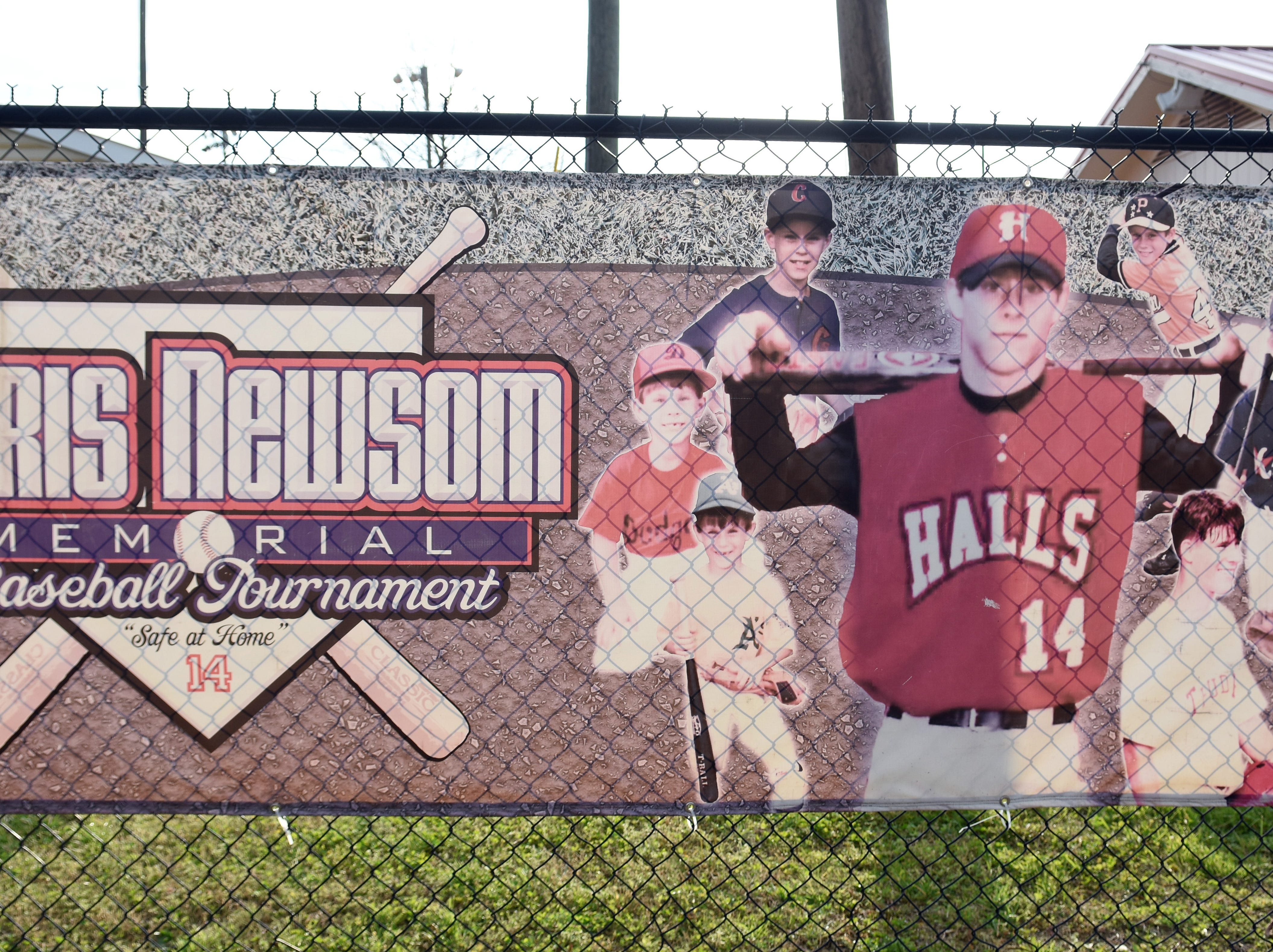 This banner remembering Chris Newsom hangs on the fence at Halls Community Park, host of the annual Chris Newsom Memorial Tournament. The park has hosted the tournament since it was established in 2008.