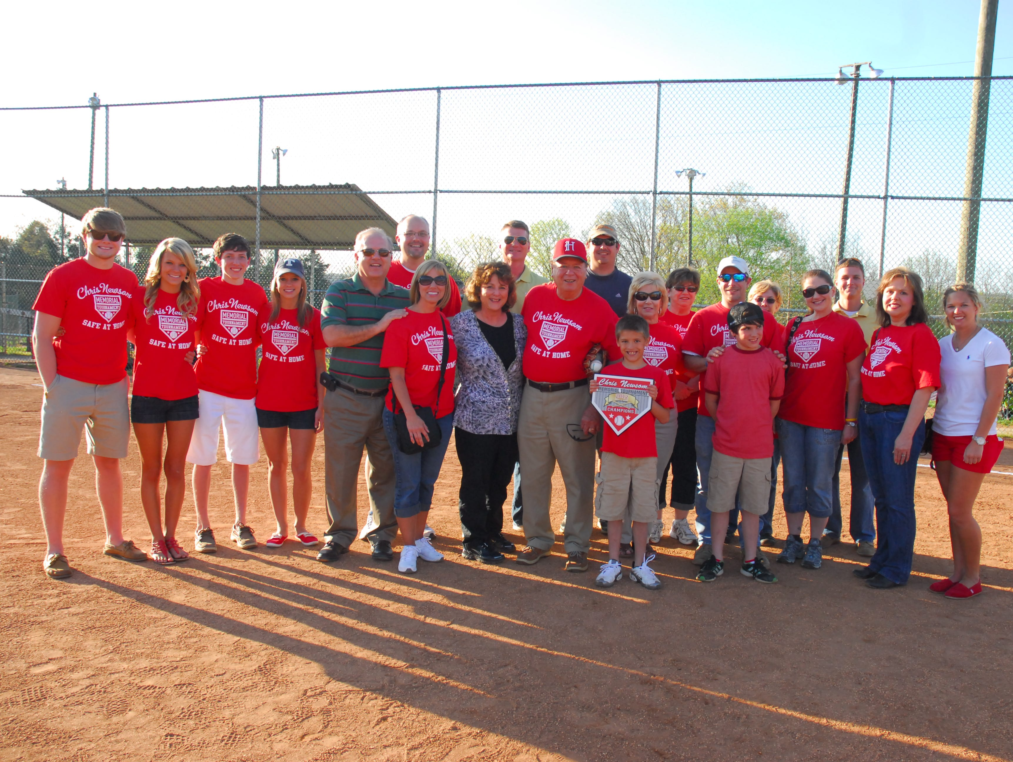 Hugh and Mary Newsom gathered on the field at Halls Park and are surrounded by family and friends at the opening of the tournament in 2012.