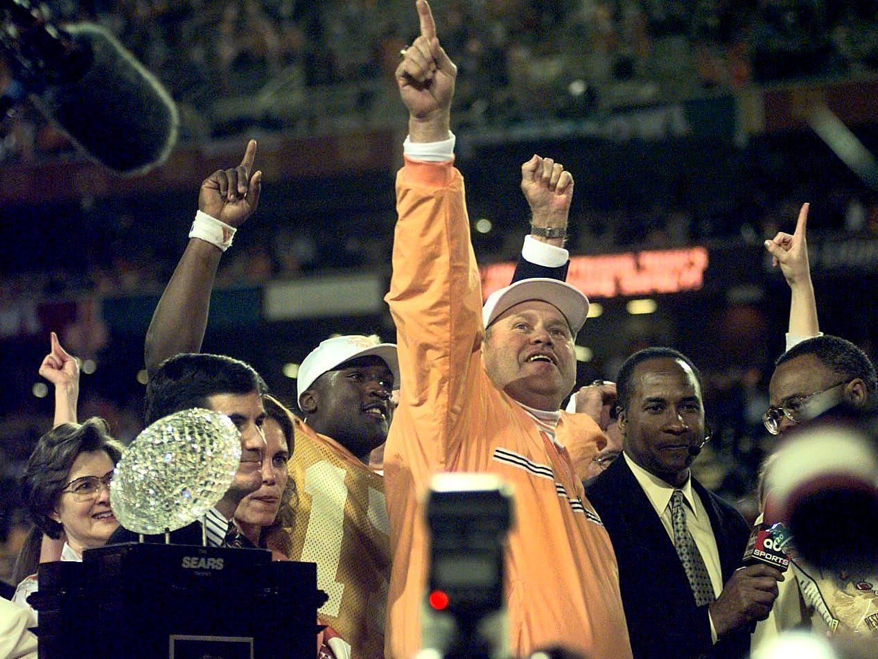 Tennessee football head coach Phil Fulmer celebrates on stage with quarterback Tee Martin behind him and the Sears National Championship trophy Jan. 4, 1999, in Tempe, Arizona. The Vols went 13-0 and finished with a Fiesta Bowl triumph over Florida State to win the national title.