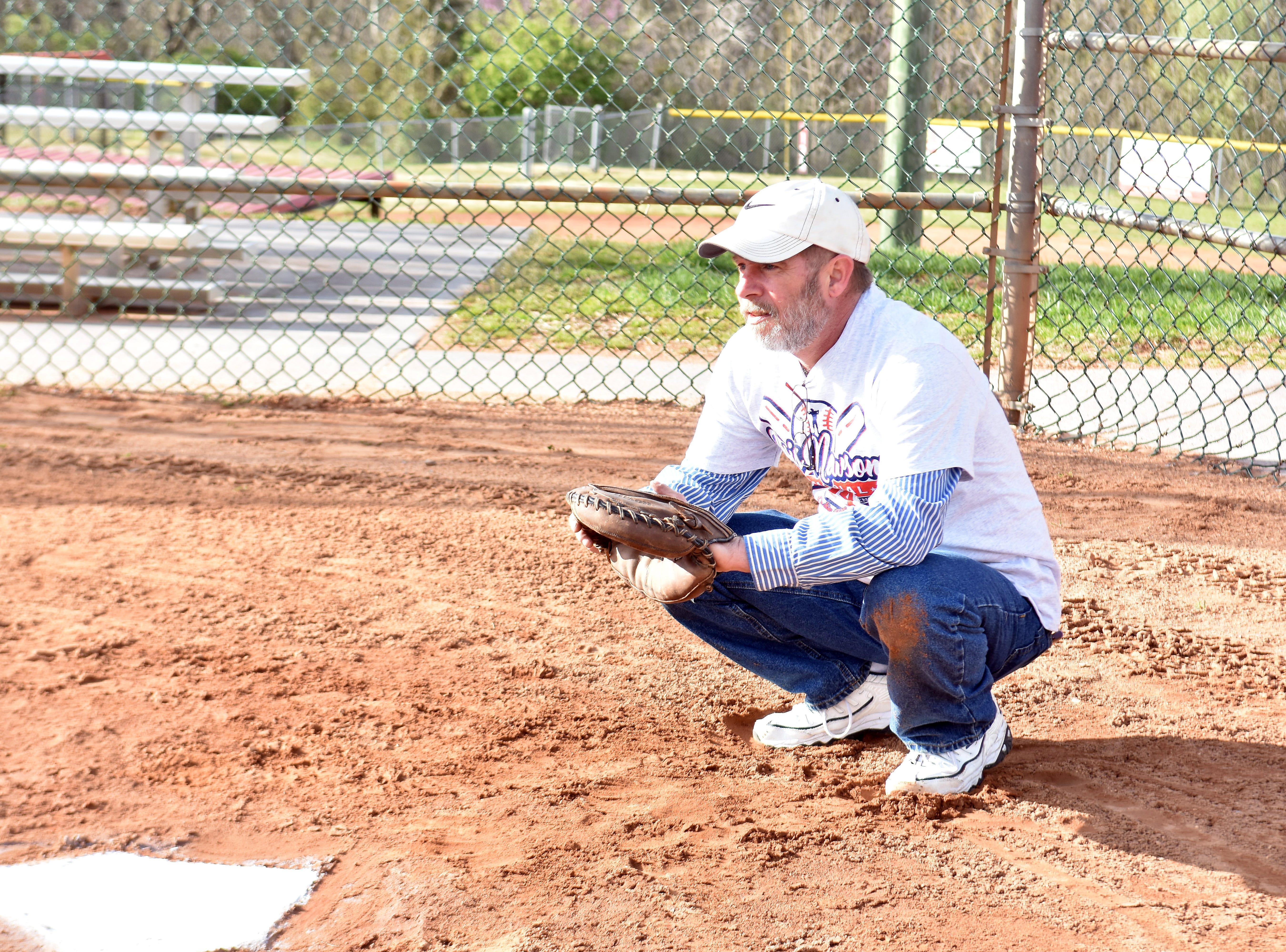 Chris Newsom's brother, Dennis Perry, serves as catcher as Hugh Newsom throws out the first pitch of the 2019 Chris Newsom Memorial Tournament.