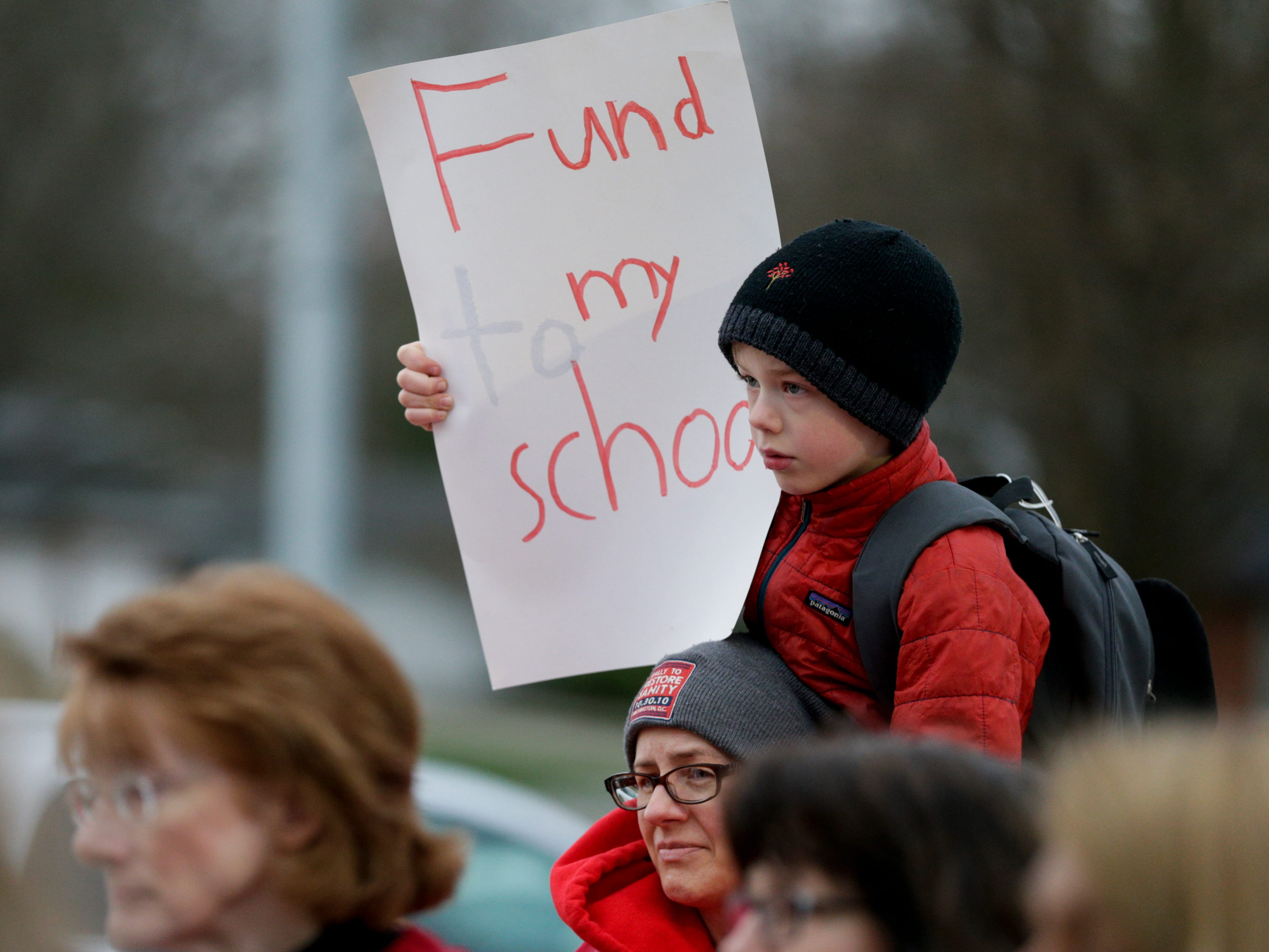A boy sits on his mother's shoulders as teachers and community members gather outside of Cumberland Elementary School, Wednesday, April 10, 2019, in West Lafayette. Greater Lafayette teachers and community members gathered outside schools before walking in to demand teacher salary raises.(Nikos Frazier   Journal & Courier)