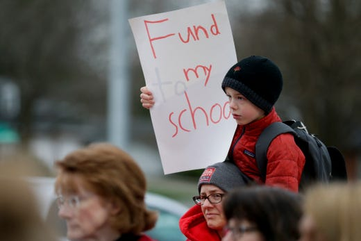 A boy sits on his mother's shoulders as teachers and community members gather outside of Cumberland Elementary School, Wednesday, April 10, 2019, in West Lafayette. Greater Lafayette teachers and community members gathered outside schools before walking in to demand teacher salary raises.  (Nikos Frazier | Journal & Courier)
