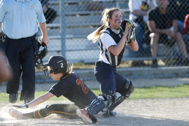 Harrison catcher Kiley Goff (11) looks towards first after outing McCutcheon right fielder Ashlyn Cheesman (2) during the fourth inning of a high school softball game, Tuesday, April 9, 2019, at Harrison High School in Lafayette. Harrison won, 8-5.  (Nikos Frazier | Journal & Courier)