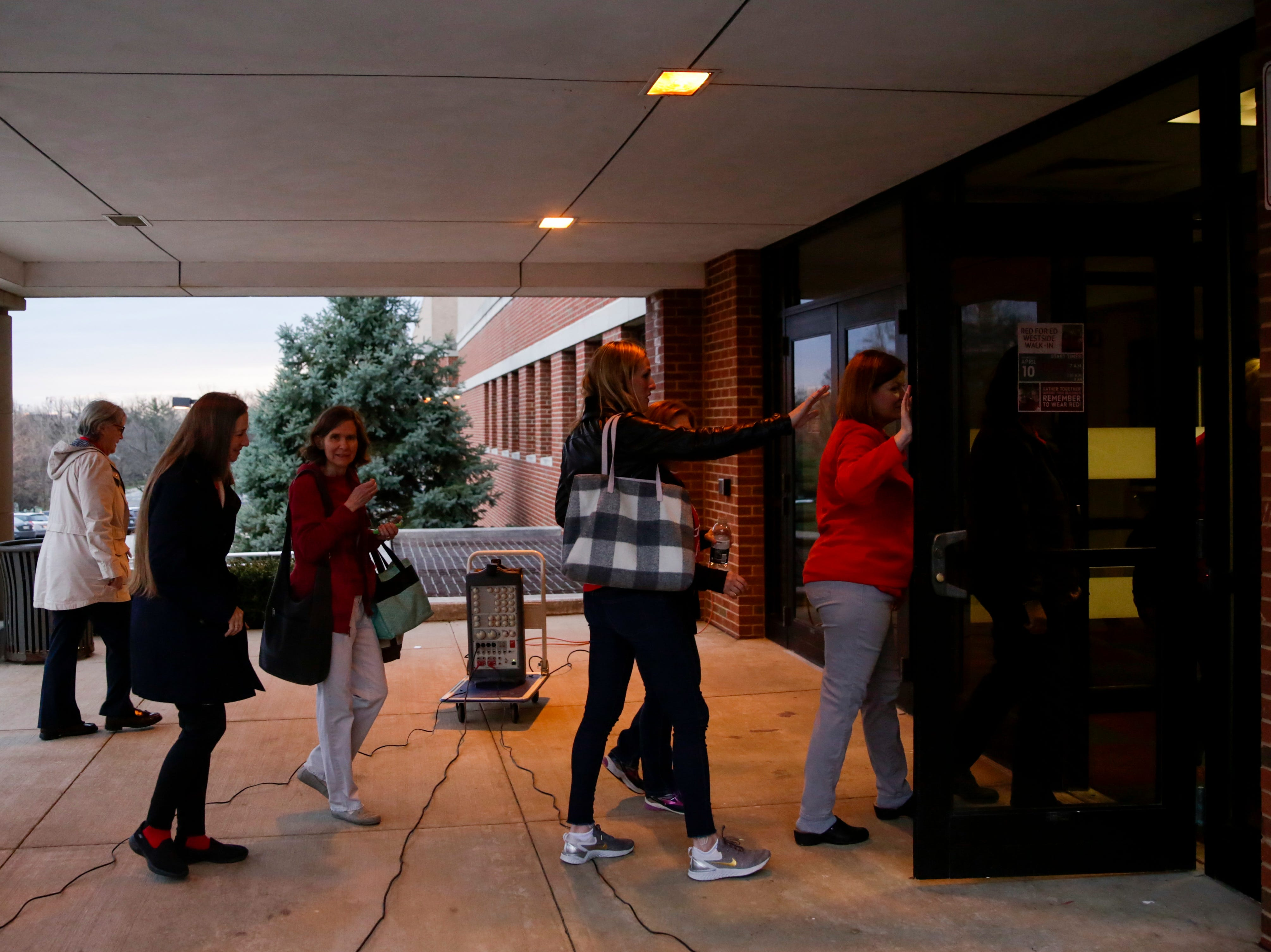 Teachers walk in after gathering outside of West Lafayette Jr./Sr. High School to bring attention to teacher salary raises, Wednesday, April 10, 2019, at West Lafayette Jr./Sr. High School in West Lafayette. Greater Lafayette teachers and community members gathered outside schools before walking in to demand teacher salary raises.(Nikos Frazier   Journal & Courier)