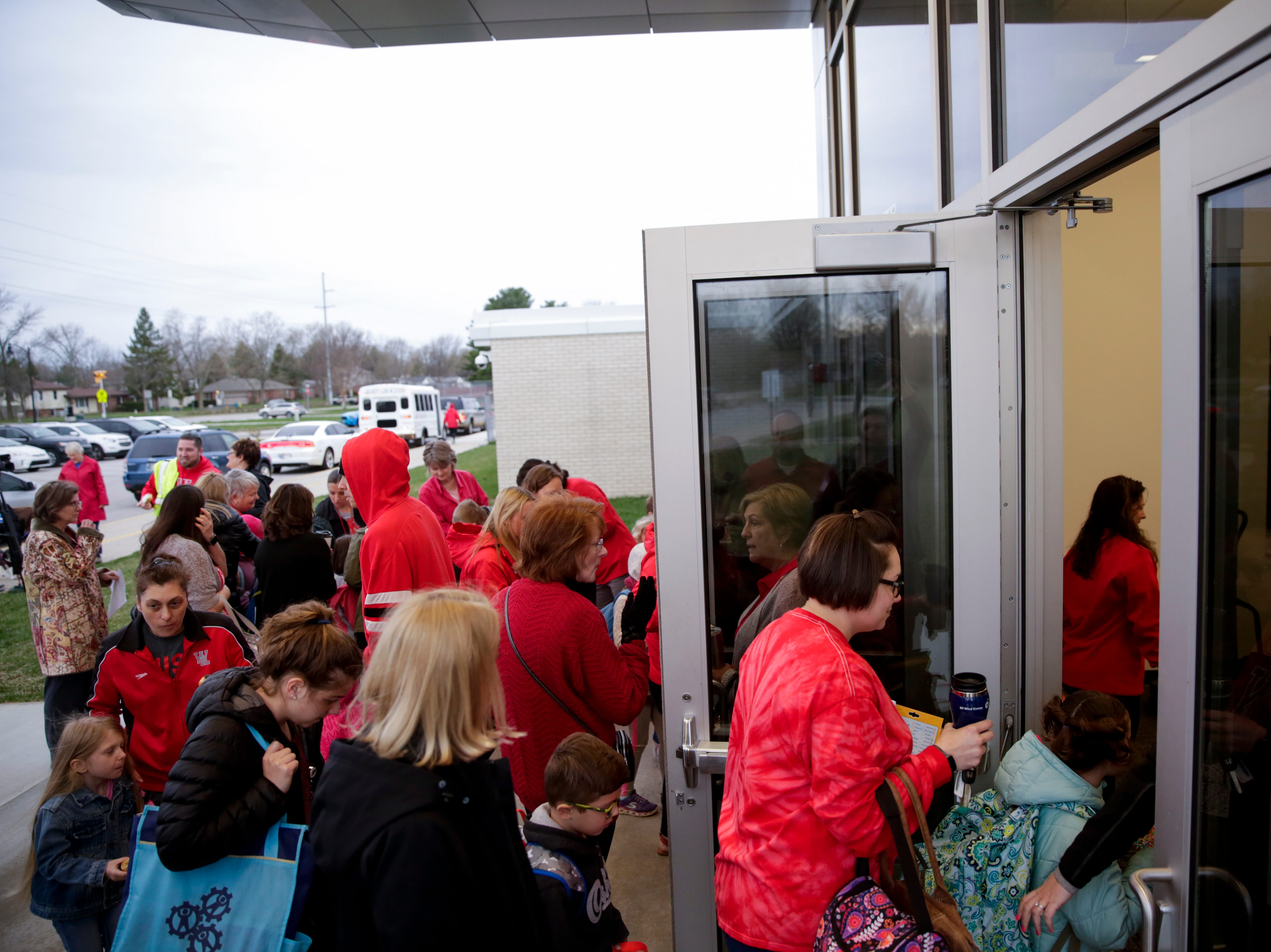 Teachers walk in to Cumberland Elementary School after gathering outside, Wednesday, April 10, 2019, at Cumberland Elementary School in West Lafayette. Greater Lafayette teachers and community members gathered outside schools before walking in to demand teacher salary raises.(Nikos Frazier   Journal & Courier)