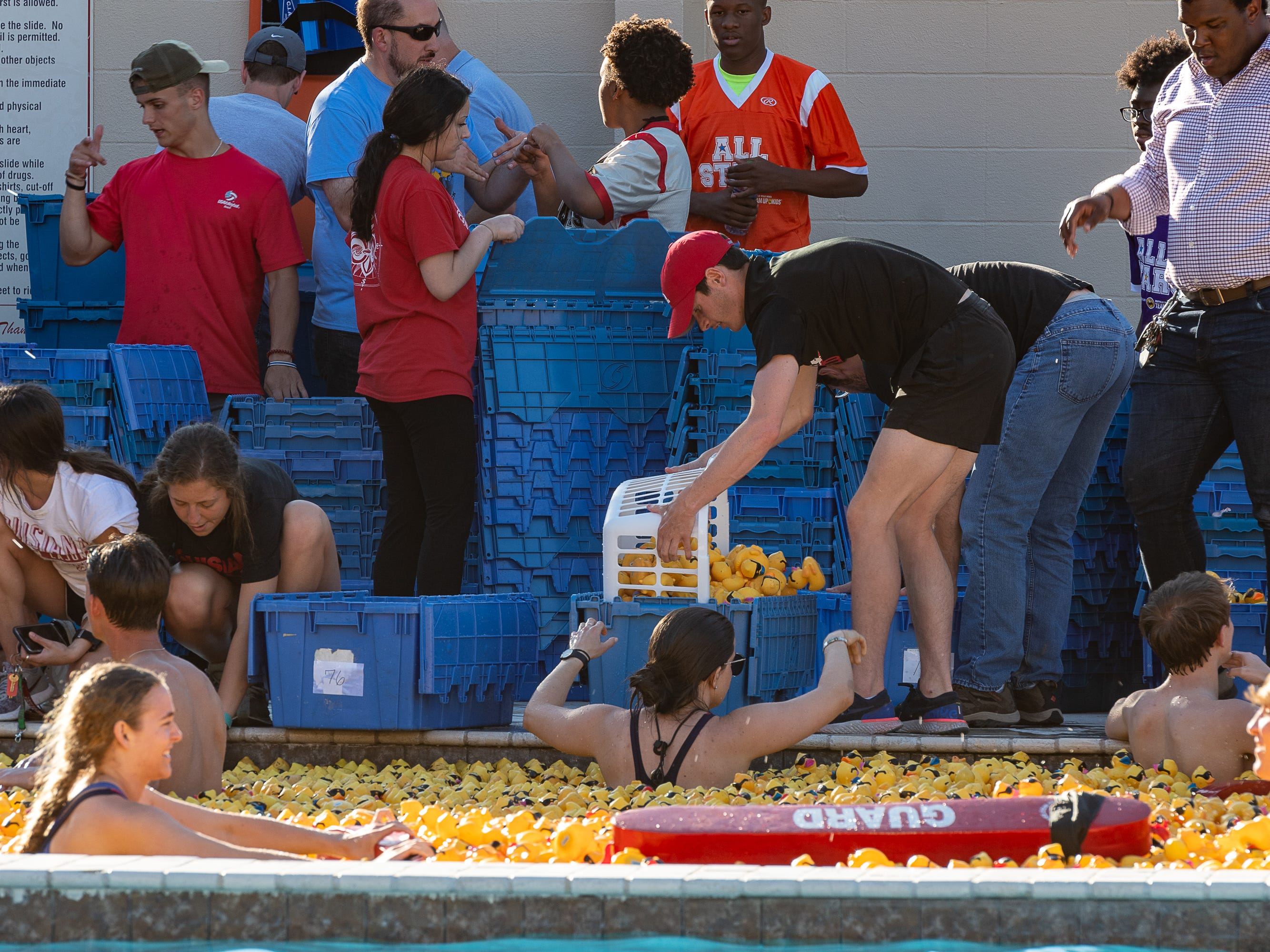 Volunteers work to collect all of the ducks at The Great Acadiana Running of the Ducks. Wednesday, April 10, 2019.