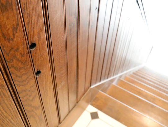 Holes in the staircase wainscoting are reminders of the wood's previous life as floor joists in the Mithoff building.