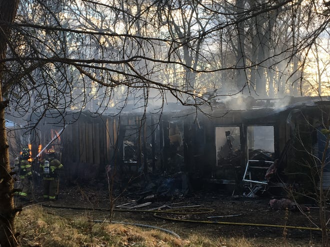 Hamburg Township firefighters use a hose to put out a fire on Tuesday April 9, 2019 at a home on the 11000 block of McGregor Road in the township. It was determined that embers from a burning leaf pile nearby caused the fire.