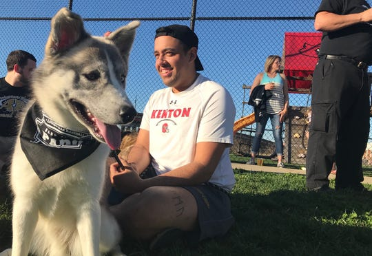 Matt Payton sits with his dog, Sky, an 11-month-old Husky Lab mix, at Louisville baseball's inagural Bark at the Park event.