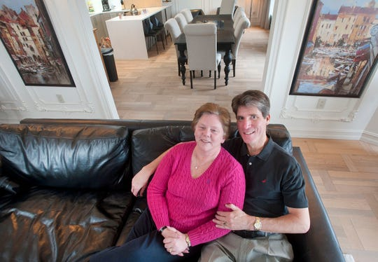 The home of Tracy and Jeff Frazier in the living room of their 1400 condominium. The open-concept dining room-kitchen can be seen behind them.