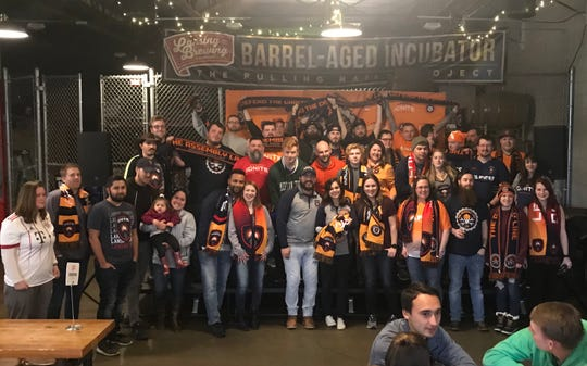 Members of The Assembly Line, Lansing Ignite's supporter's group, gather for a photo at Lansing Brewing Company during the team's first game vs. Richmond on March 30.