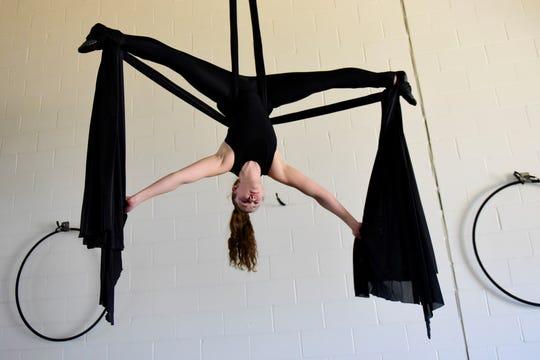 Tori Chandler, of Galion, hangs from yoga aerial silks inside the new Evolve Studio in Lexington.
