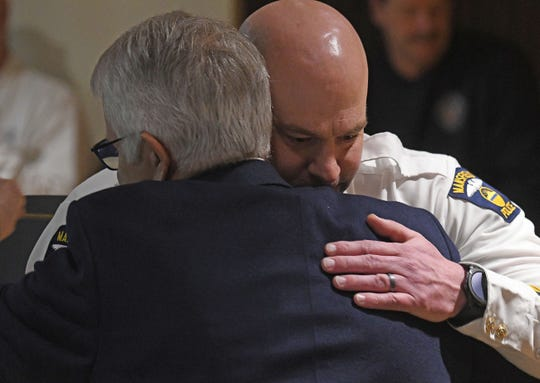 Newly sworn-in police chief Keith Porch hugs Mansfield Mayor Tim Theaker after taking his oath.