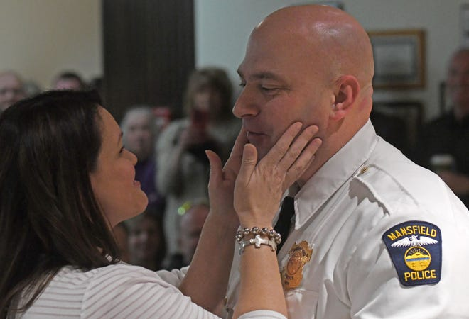 Newly sworn-in Mansfield police chief, Keith Porch, receives a kiss from his wife Julie after she pinned his new badge on him Wednesday morning.