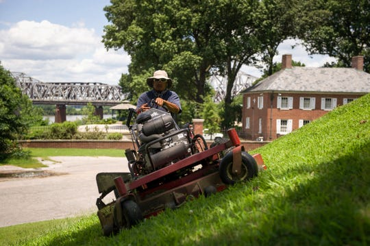 July 16, 2014 - Alex Angelos mows the grass along the side of a Native American mound at Chickasaw Heritage Park. Behind him the Harahan, Frisco and Memphis & Arkansas bridges are visible as well as the National Ornamental Museum. All of the landmarks are located in the French Fort district south of Downtown Memphis, which developer Lauren Crews plans to redevelop.