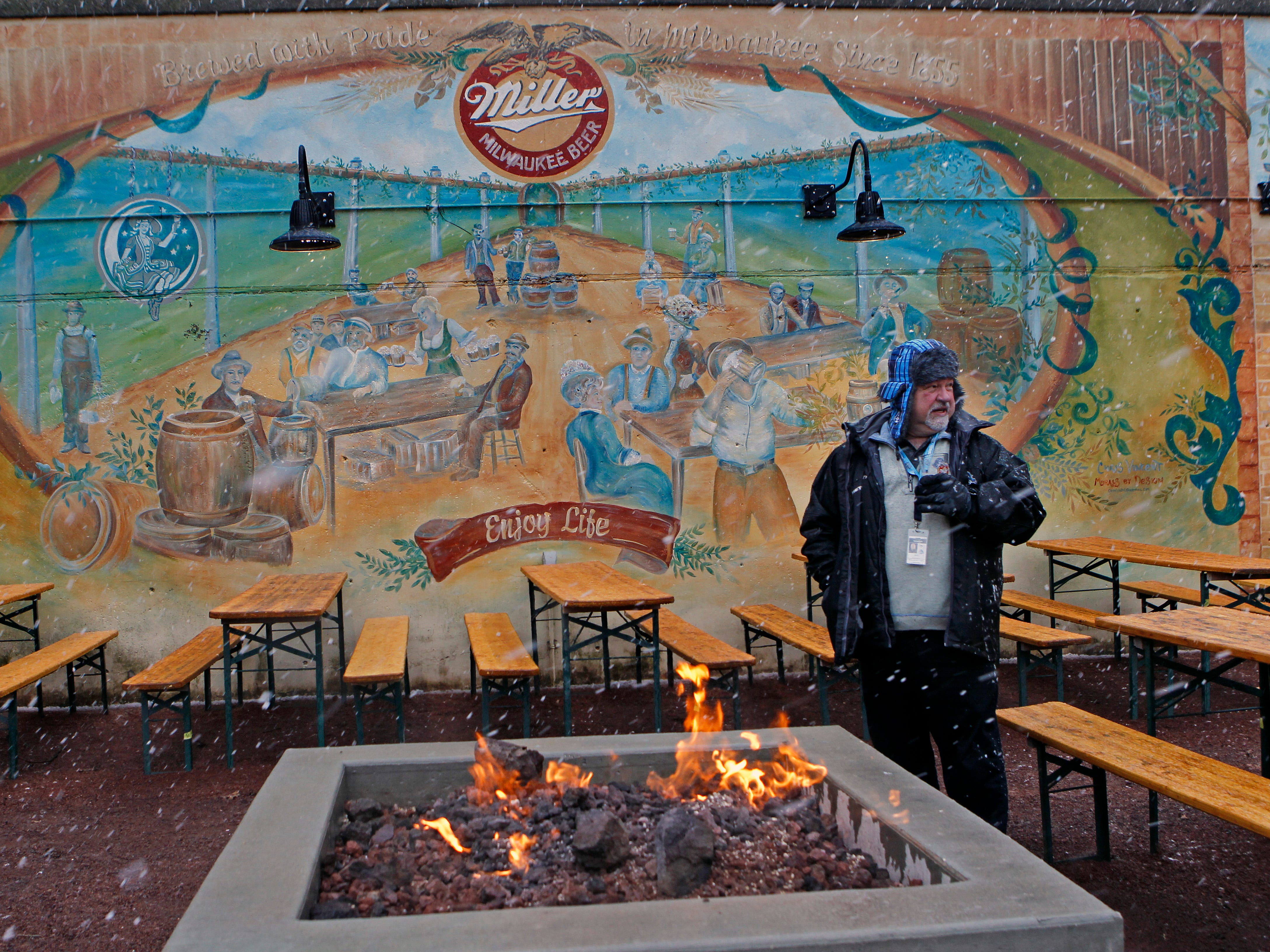 Mike Wojciechowski warms up with a beer near the fire while attending a beer garden kick off at South Shore Terrace on Wednesday.