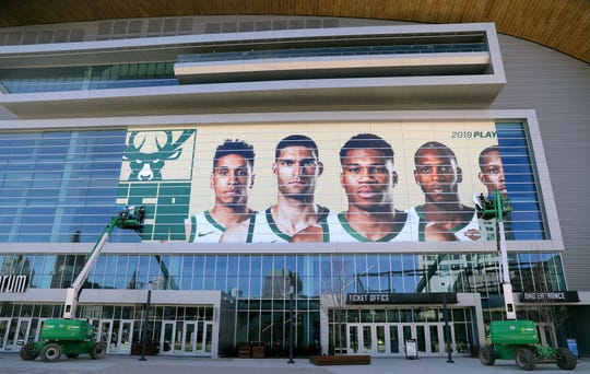 Workers from Signs & Lines by Stretch get Fiserv Forum ready for the upcoming NBA playoffs by putting a photo of the Bucks' starting five on the windows facing the plaza just outside the new arena.