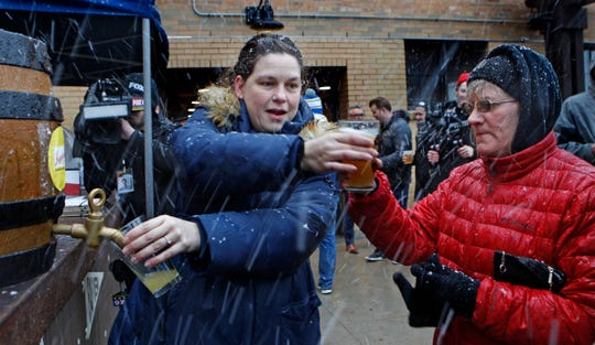 Andrea Wallace (left), food and beverage manager for Milwaukee Parks, serves beer to Debbie Peterson  on Wednesday at the South Shore Terrace. Even with a spring snow show several hundred turned out for the event that featured free beer and food.