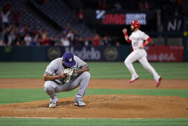 Milwaukee Brewers starting pitcher Freddy Peralta squats on the mound after giving up a three-run home run to Los Angeles Angels' Tommy La Stella during the first inning of a baseball game Tuesday, April 9, 2019, in Anaheim, Calif. In the background is Angels' Jonathan Lucroy. (AP Photo/Jae C. Hong) ORG XMIT: ANS103