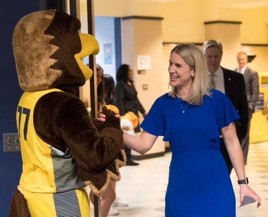 Marquette women's basketball coach Megan Duffy is greeted by the school mascot before an introductory news conference  Wednesday, April 10, 2019 at Marquette University in Milwaukee, Wis. 