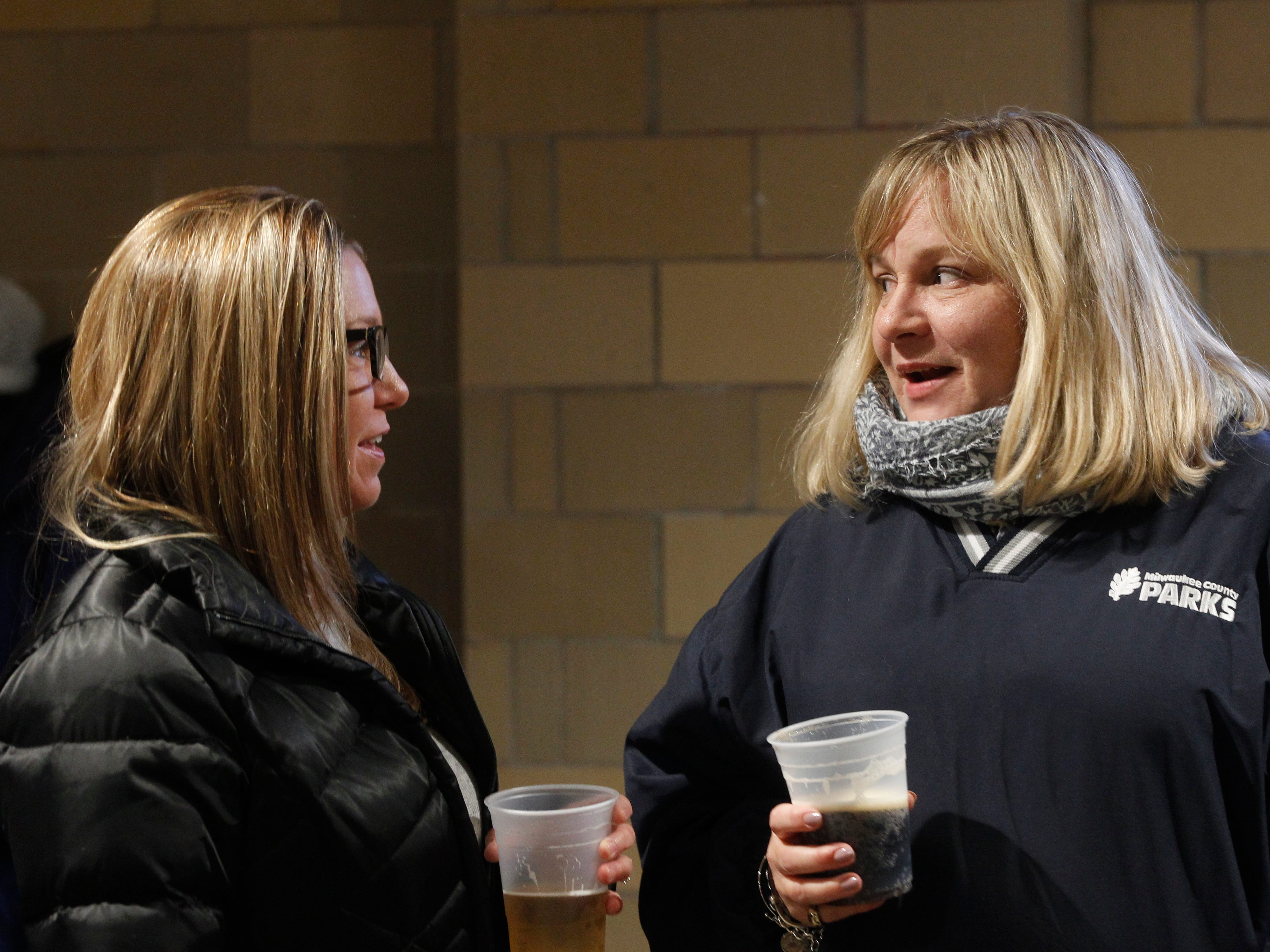 Michelle Smith (left) and Paula Johnson, talk while waiting in the food line at  South Shore Terrace on Wednesday.