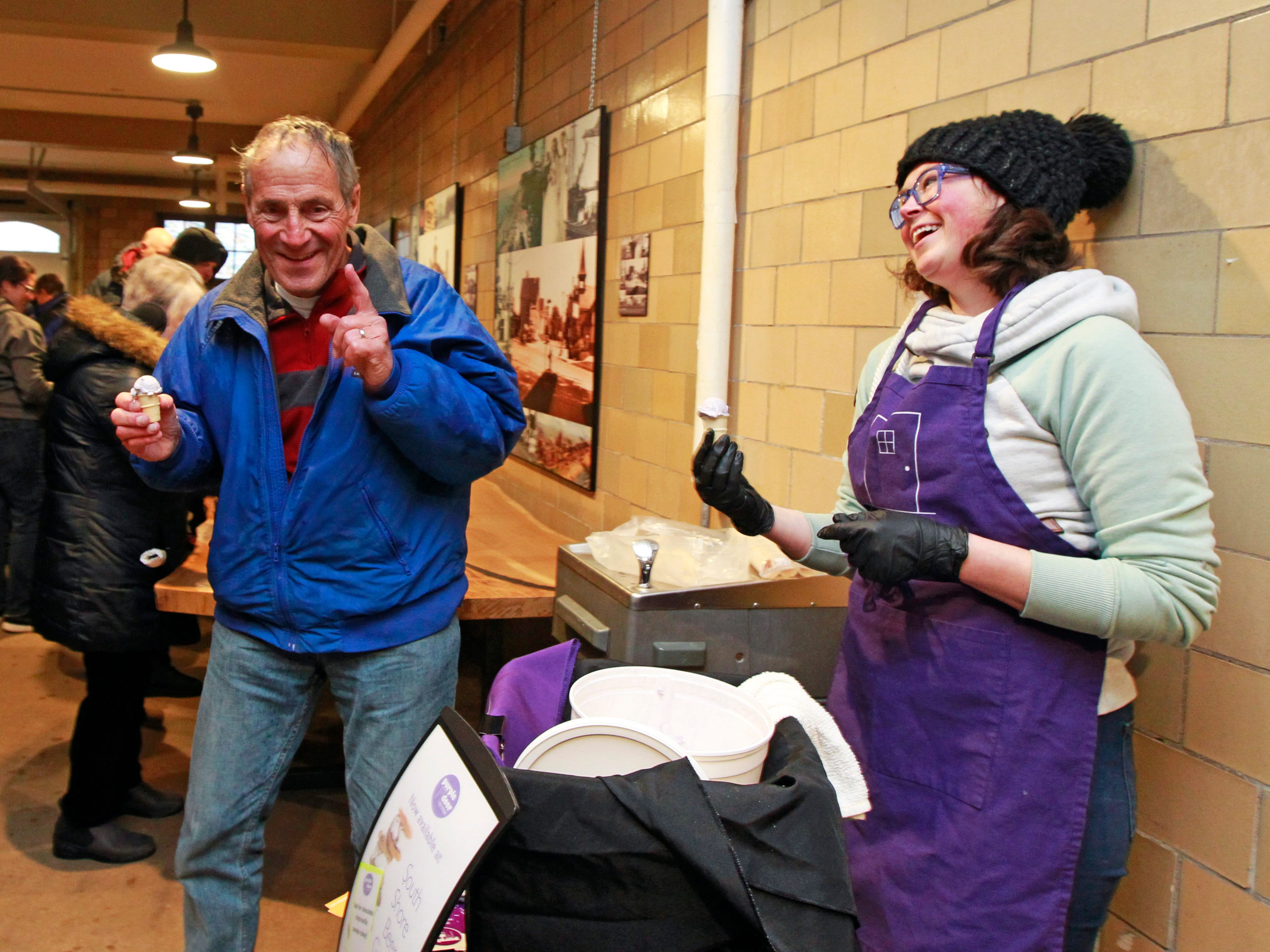 Lindsay Stayton Mannebach (right), from Purlple Door Ice Cream, offers the company's new flavor -- Purple Moon --  to those attending the beer garden at South Shore Terrace on Wednesday.