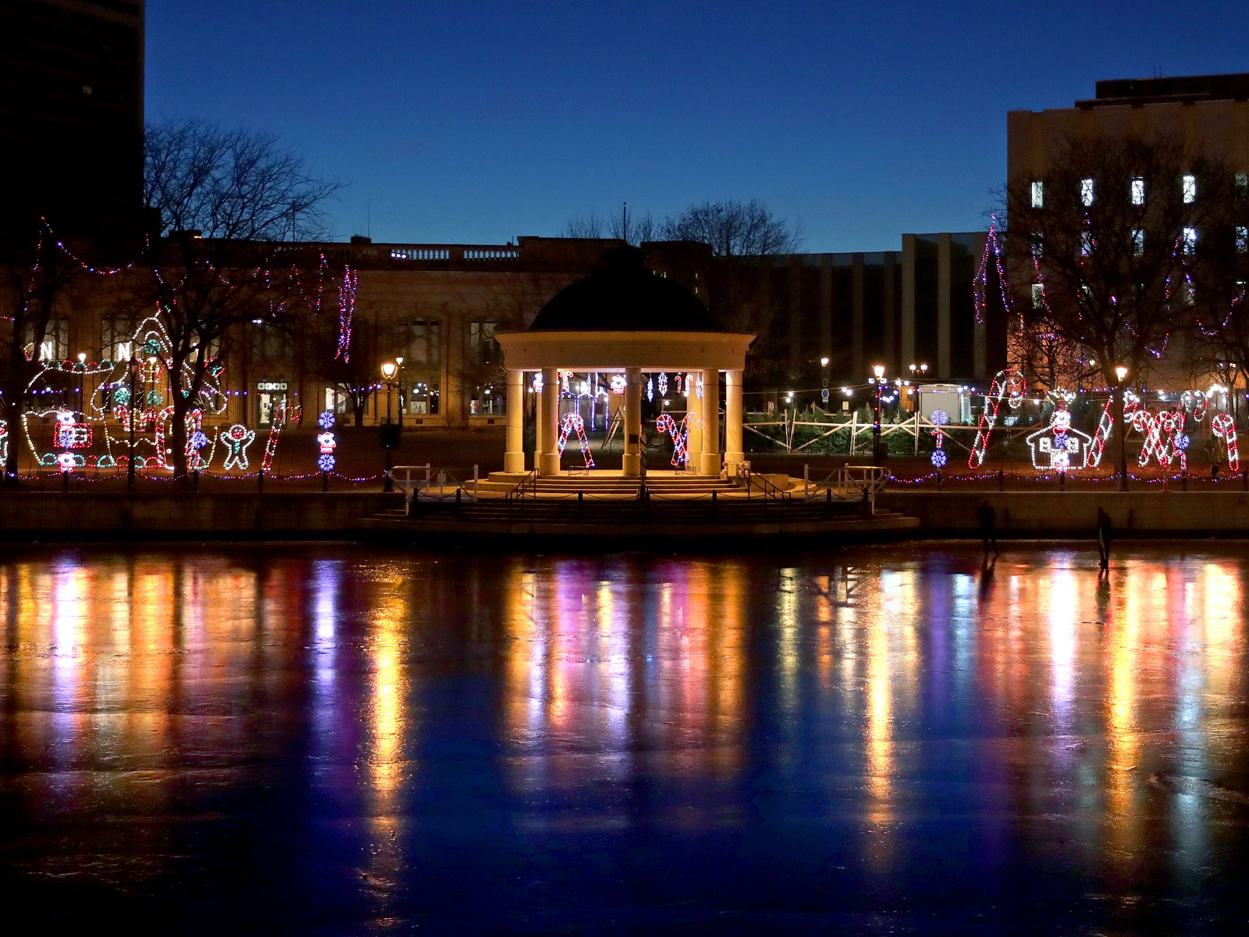 Christmas lights reflect on the Milwaukee River from Pere Marquette Park.