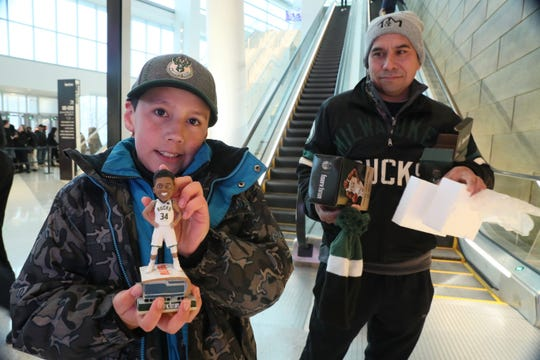 Israel Benitez age 10 of Milwaukee and his father Louis Benitez (right) both were among the first in the door and each got a bobblehead of Giannis Antetokounmpo.