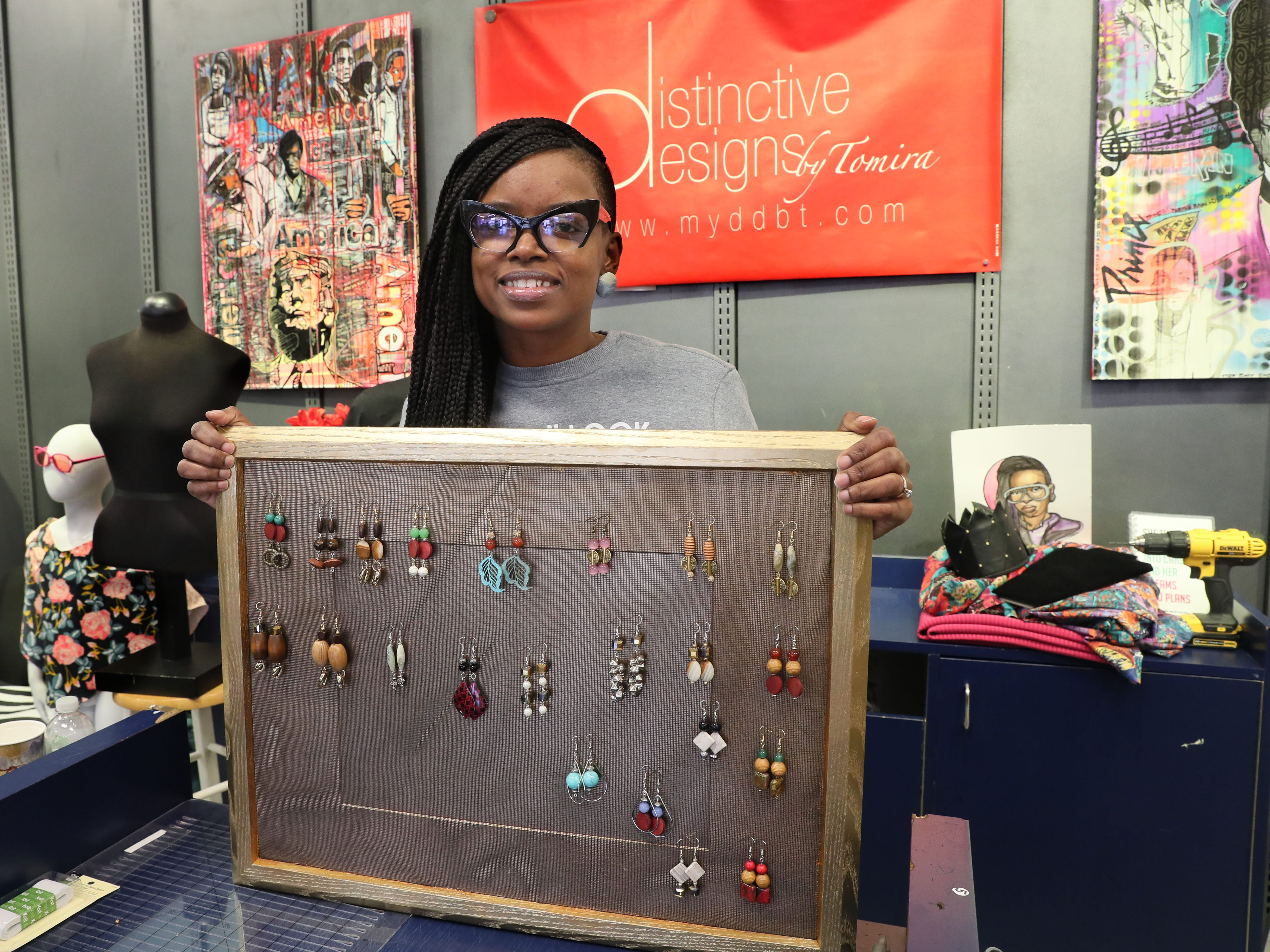 Tomira White displays earings she designed for The Bronzeville Collective.