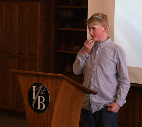 Pinkston Middle School sixth-grader Stone Ramsey speaks into a microphone Wednesday while talking about his time shadowing Baxter County Tax Collector Teresa Smith on Monday as part of the Kiwanis' Student Government Day.
