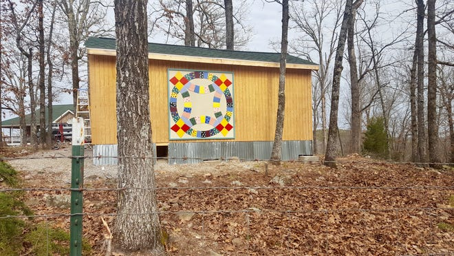 """The """"Double Wedding Ring"""" can be found at 113 Ivanhoe in the Buffalo City community. Pam Wise and her son, Jonathan, designed and constructed this 6'x6' unique block by cutting 72 different tiles of eight different shapes, which were generated using a computer program. The """"fabric"""" patterns were cut from vinyl and applied to the tiles."""