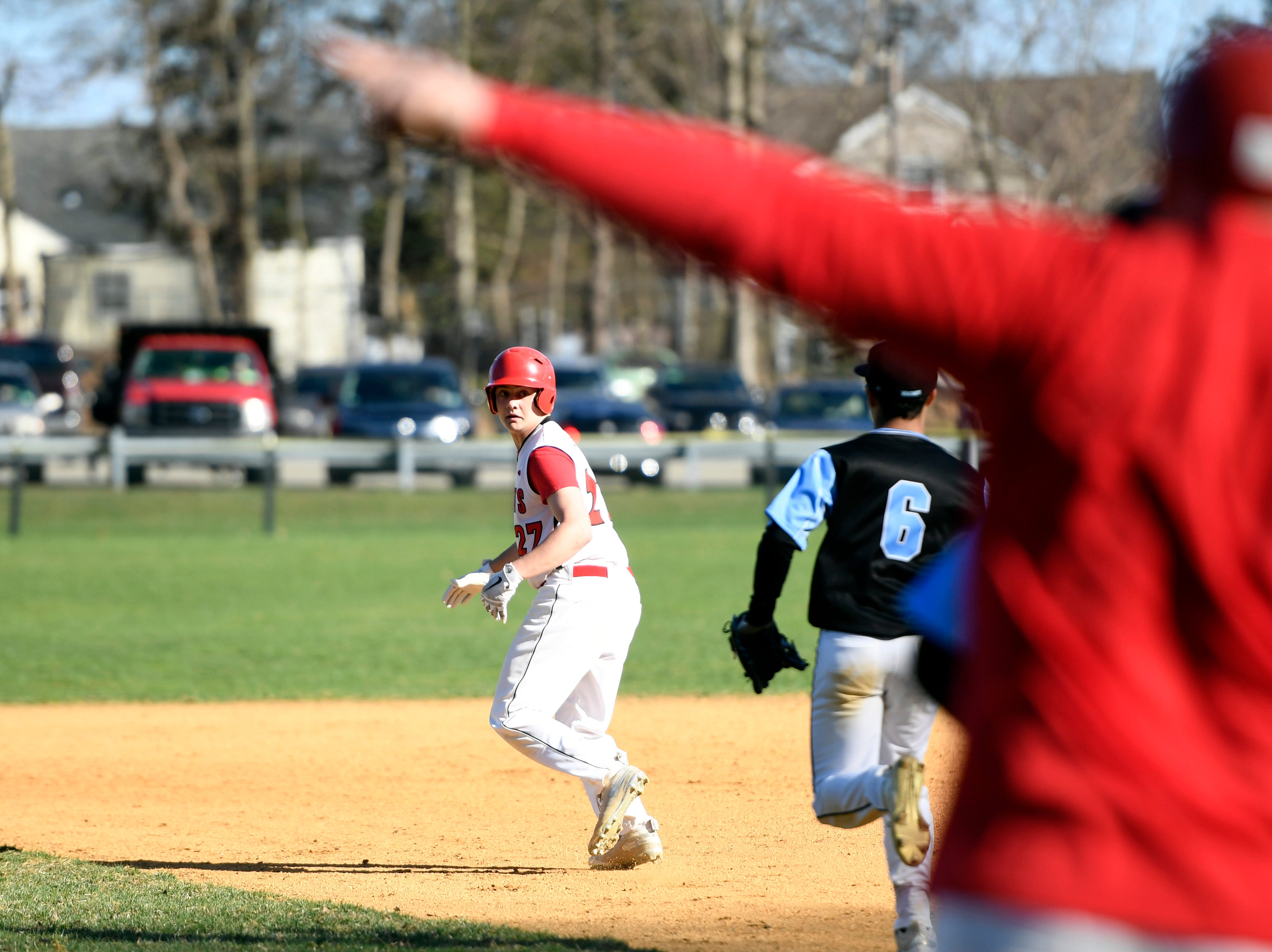 Morris Hills runner Nick Carlotti (27) runs towards second away from a tag from Parsippany Hills' Ty Sallie (8) as Morris Hills head coach Bret Giovine, right, instructs from the sideline on Wednesday, April 10, 2019, in Rockaway.