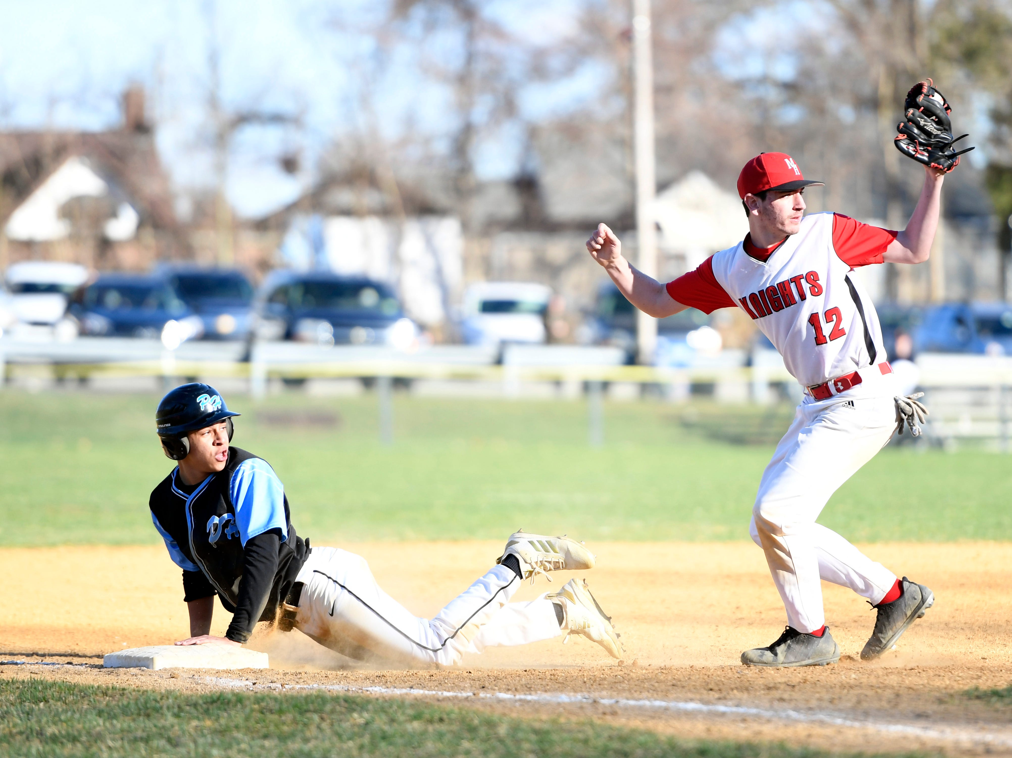 Morris Hills third baseman Jack Sautter (12) and Parsippany Hills runner Ty Sallie look to the base umpire after Sallie is tagged out on Wednesday, April 10, 2019, in Rockaway.