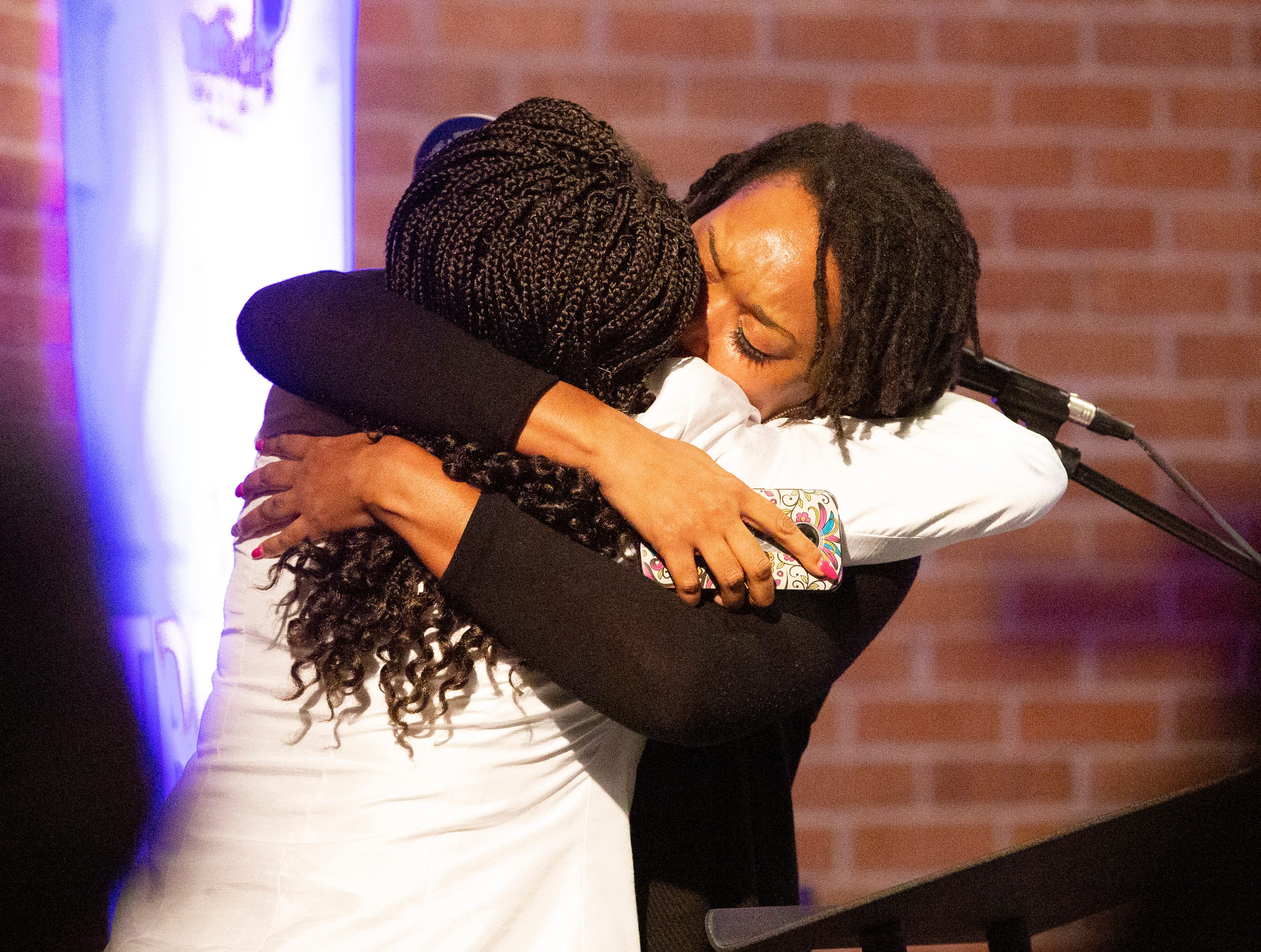 Furlesia Bell comforts Marquitta Arrington as she tries to speak on the process of grieving for their lost loved one. Arrington lost her son.