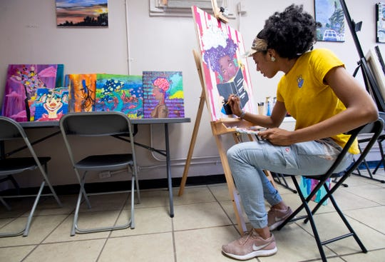 SaQuia Evans paints in The King's Canvas art space in Montgomery, Ala., on Wednesday April 10, 2019.