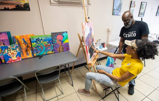 Kevin King works with SaQuia Evans as she paints in The King's Canvas art space in Montgomery, Ala., on Wednesday April 10, 2019.