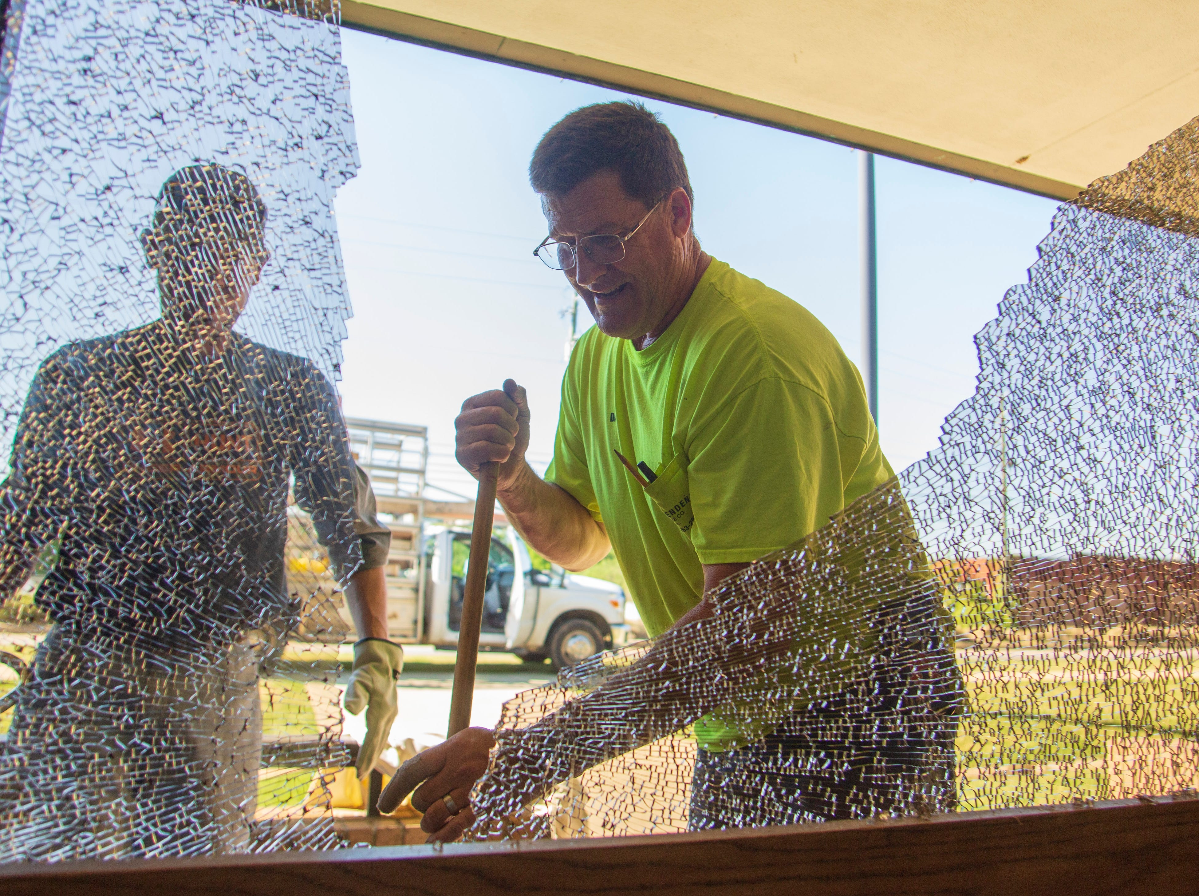 Conrad Ward and Dale Vickers gather glass from a Salvation Army window that'd been damaged by a rock.