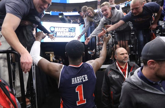 Auburn guard Jared Harper high fives fans as he walks of the court an NCAA Tournament second round win over Kansas on Saturday, March 23, 2019, in Salt Lake City.