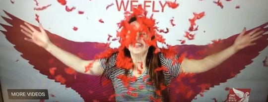 A woman plays in confetti in front of a  Cardinal wing background in a video promoting One Ball State Day.