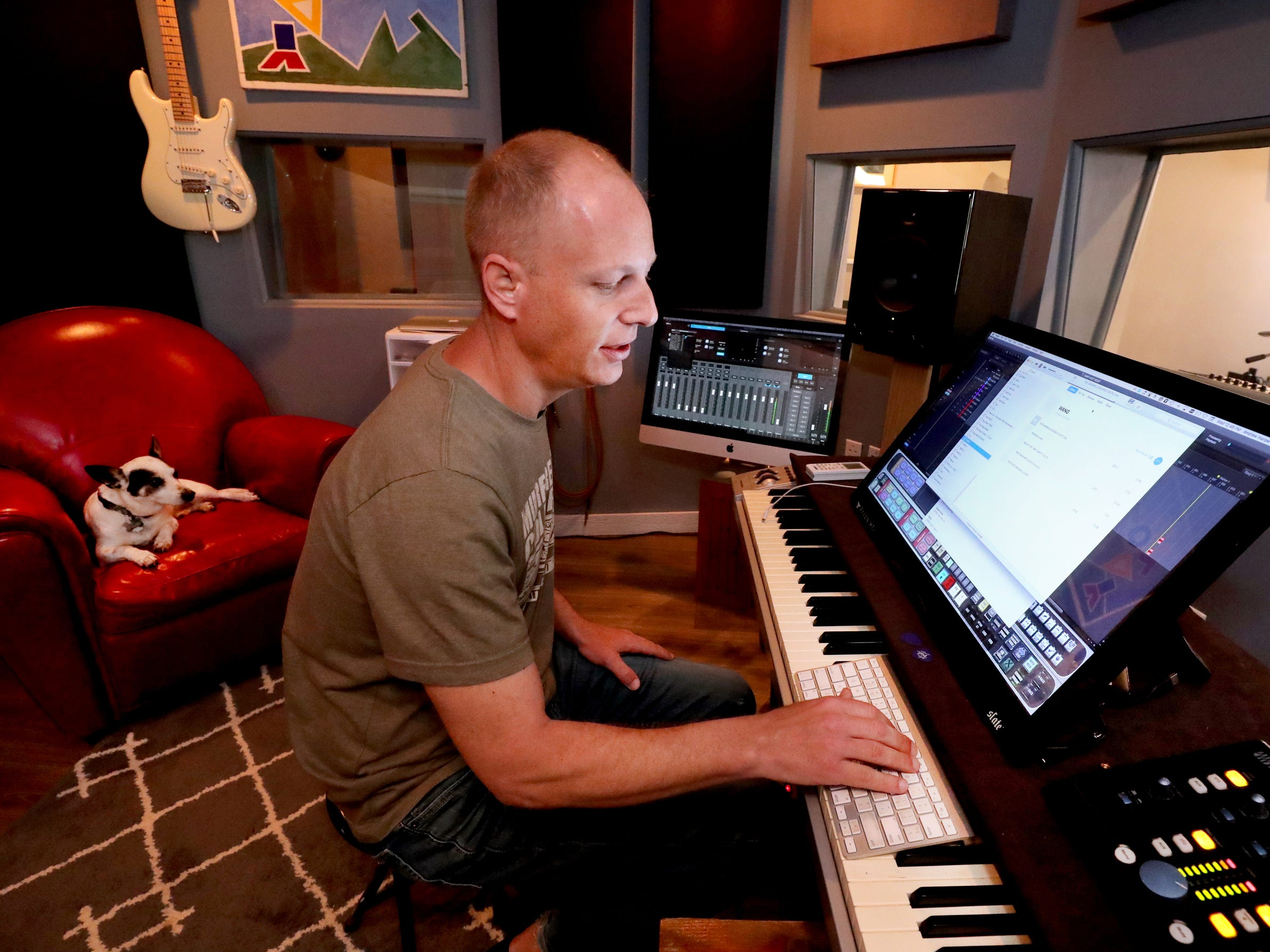 Andy Harper pulls up some pulls up some examples of his work  in his studio Limitedwave Recordings on Wednesday April 10, 2019, as his dog Jackson relaxes in the chair behind him.