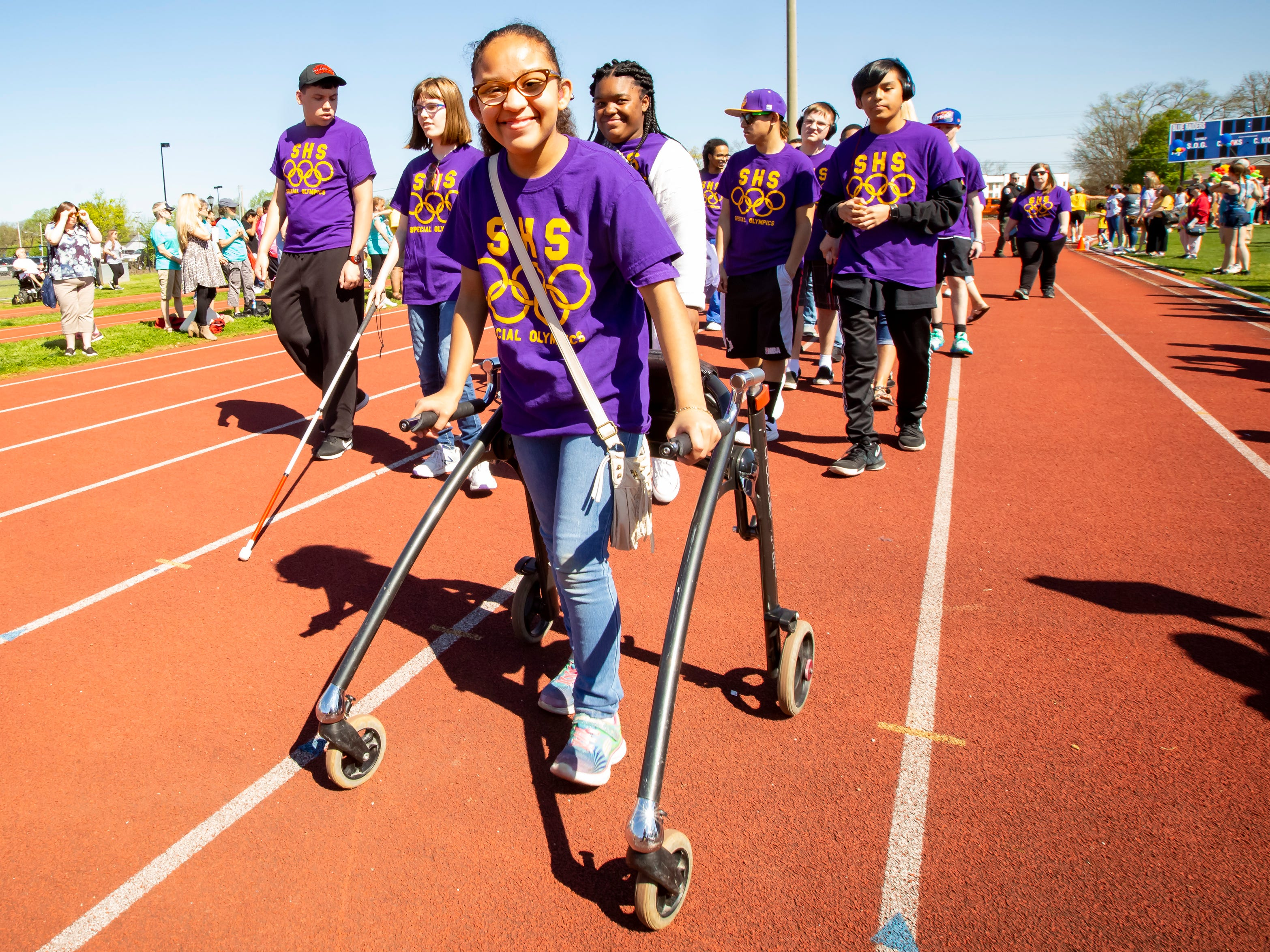 Special Olympian Jacki leads the Smyrna High School delegation during the parade of athletics before the start of Wednesday's track and field meet at MTSU.