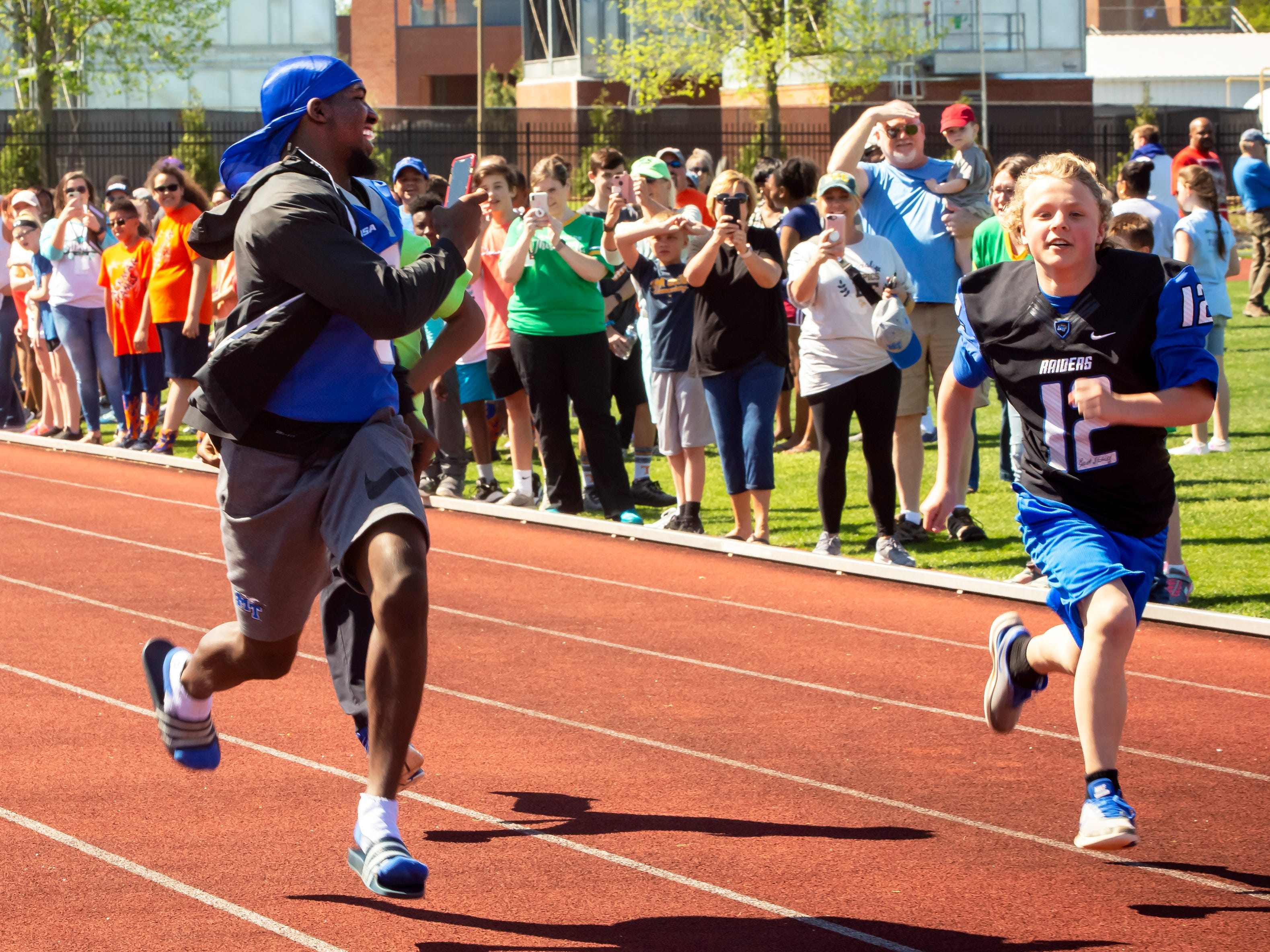 MTSU cornerback Greg Grate runs along some of the Special Olympic athletics during a heat race and videos the dash.