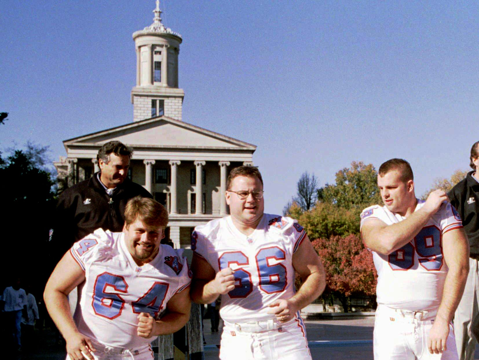 Tennessee Oilers players Erik Norgard (64) and Jason Layman (66) joke around as Jon Runyan (69) looks on before they line up for a team photo in front of the Tennessee Capitol Nov. 17, 1997 in Nashville. Wide receivers coach Alan Lowry stands behind them.