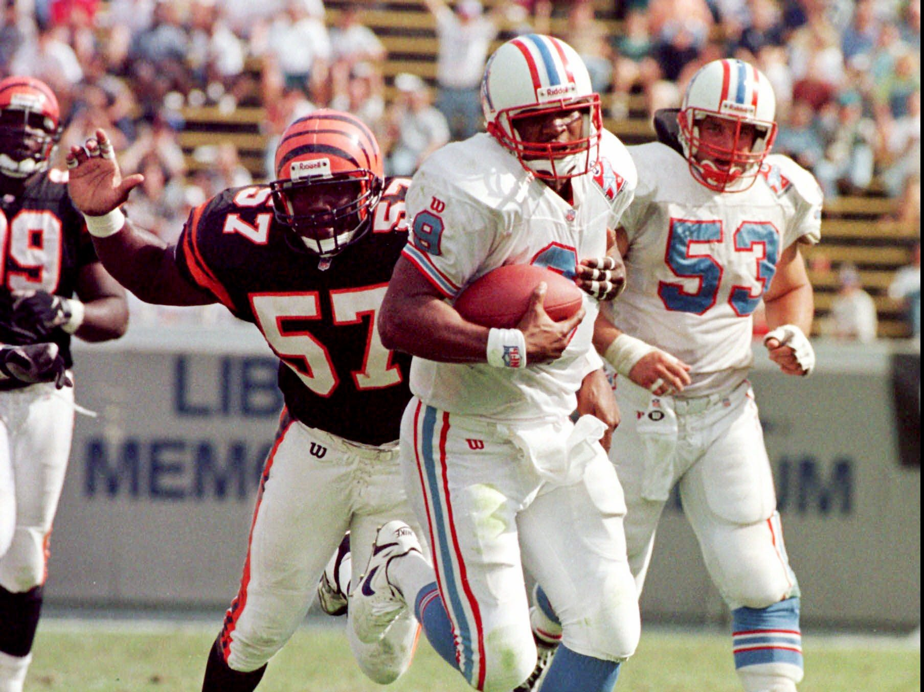 Tennessee Oilers quarterback Steve McNair, center, is chased by Cincinnati Bengals Reinard Wilson (57) as he gains 21 yards on a fourth-quarter run during the Oilers' 30-7 win Oct. 12, 1997 in Memphis. At right is Oilers center Mark Stepnoski (53).