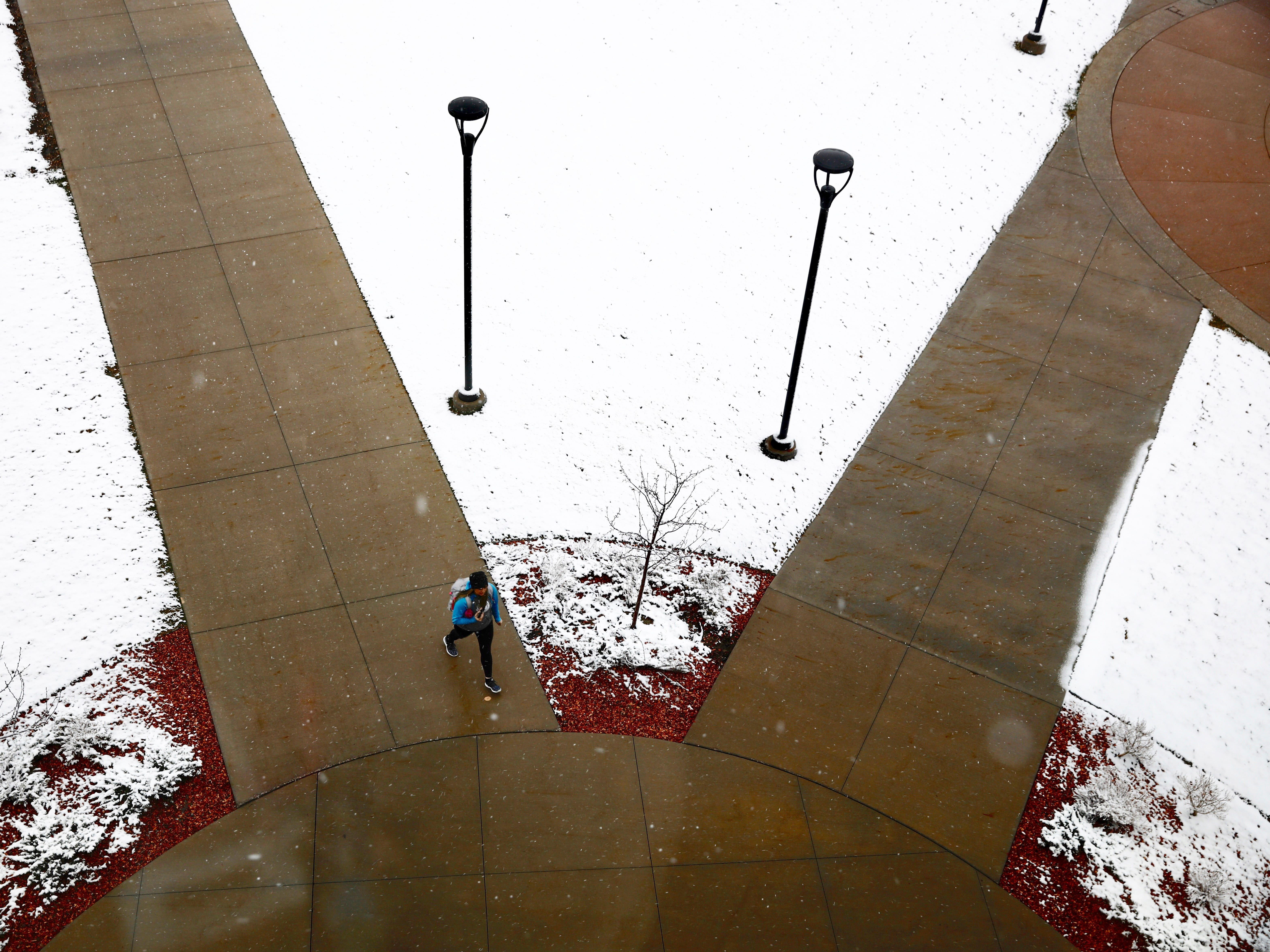 A student walks towards the Casper College student union Wednesday morning, April 10, 2019, after snow layered the grounds of the common area in Casper, Wyoming. The National Weather Services said Wednesday that a winter storm could bring up to 12 inches of snow to parts of Wyoming.