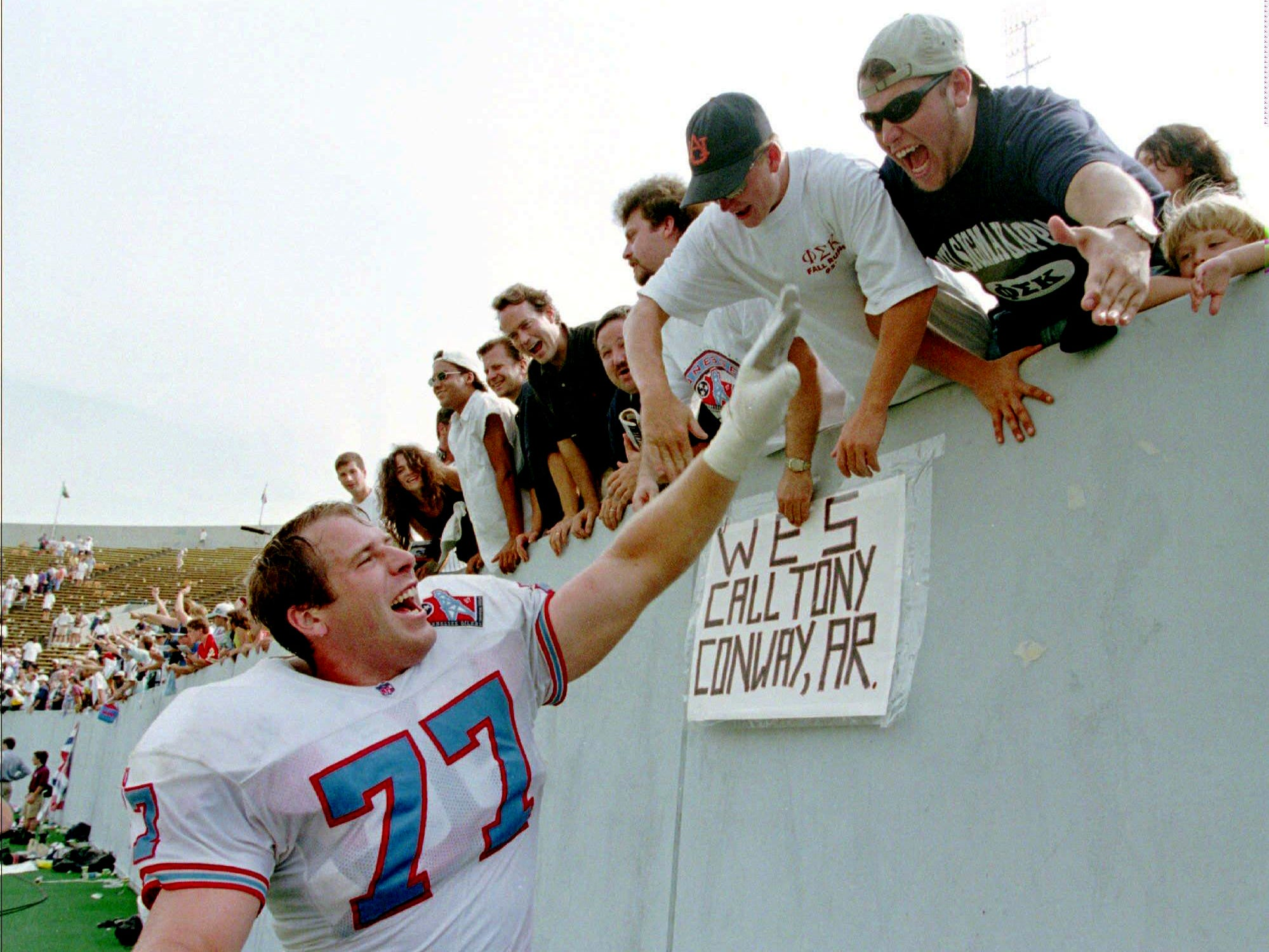 Tennessee Oilers guard Kevin Donnalley (77) celebrates with fans after the Oilers defeated the Oakland Raiders 24-21 in overtime Aug. 31, 1997 in Memphis. It was the first regular-season game for the Oilers since moving from Houston to Tennessee.