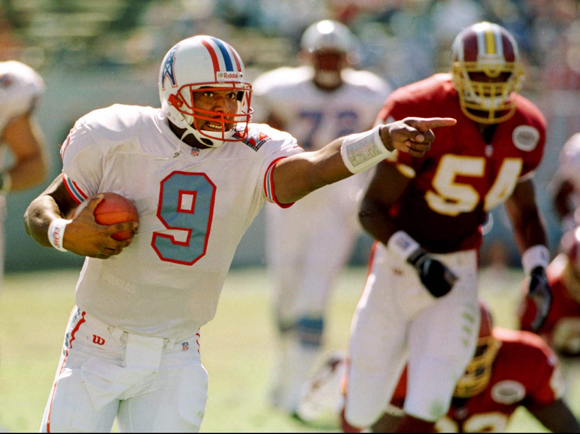 Tennessee Oilers quarterback Steve McNair directs a teammate as he runs for a two-yard touchdown in the second quarter against the Washington Redskins Oct. 19, 1997 in Memphis. McNair rushed for 53 yards and passed for 192 yards as Tennessee defeated Washington, 28-14.