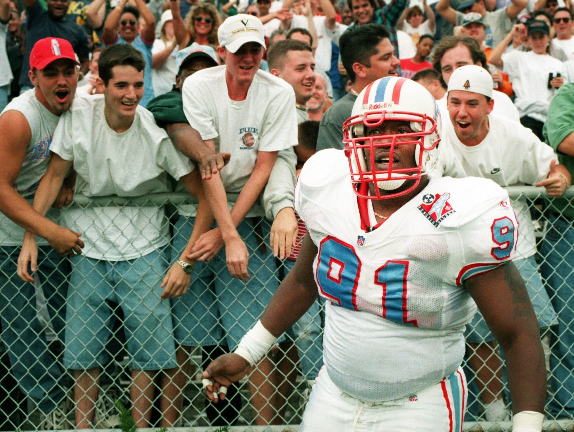 Tennessee Oilers defensive lineman Josh Evans (91) receives adulation from fans after he ran a Cincinnati Bengals' fumble for a touchdown. The touchdown was call back by officials, erasing the score by Evans. The Oilers won big, 44-14 over the Bengals at Vanderbilt Stadium Oct. 18, 1998.